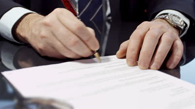 stock-footage-businessman-sitting-at-shiny-office-desk-signing-a-contract-with-noble-pen